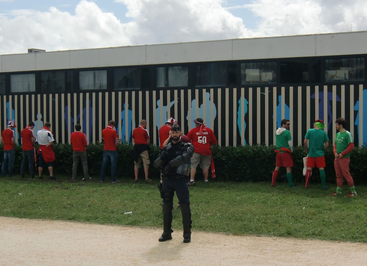 Bild von Fussballfans die ihr kleines Gescäft vor dem Spiel an einem Zaun verrichten
